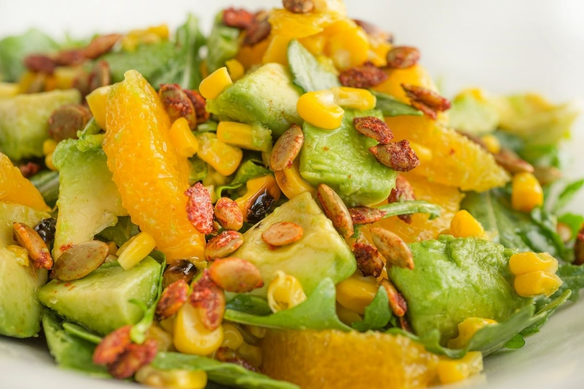 Bold and crisp close up photo of the salad showcasing the juicy mandarins and avocado with crunchy toppings.